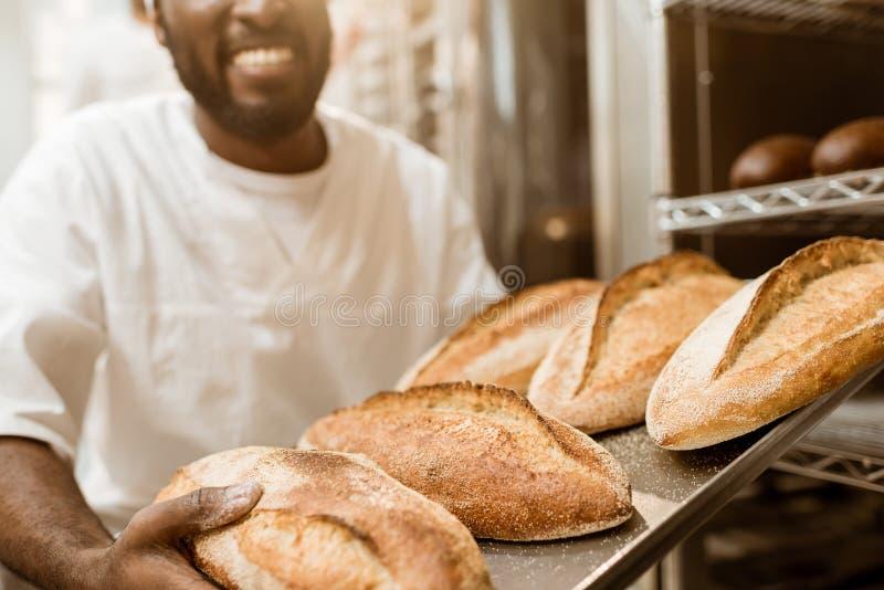 tiro cosechado del panadero afroamericano sonriente con la bandeja de barras de pan frescas fotografía de archivo libre de regalías