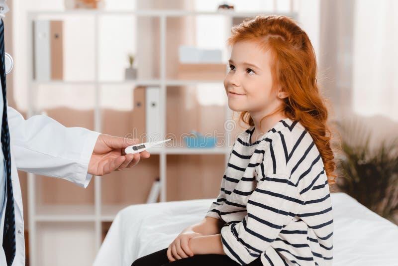 tiro cosechado del pediatra que da el termómetro a la pequeña muchacha sonriente foto de archivo libre de regalías