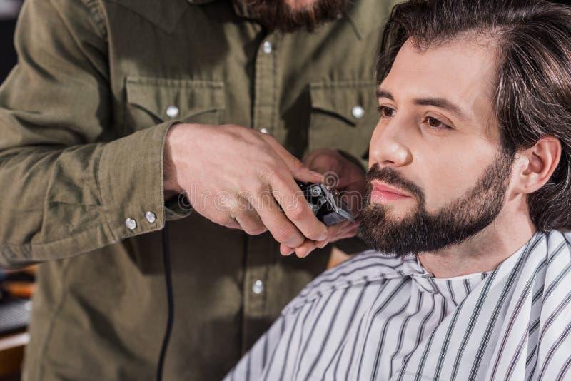 tiro cosechado del peluquero que afeita al cliente foto de archivo