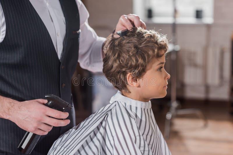 tiro cosechado del peluquero que peina el pelo del niño fotos de archivo
