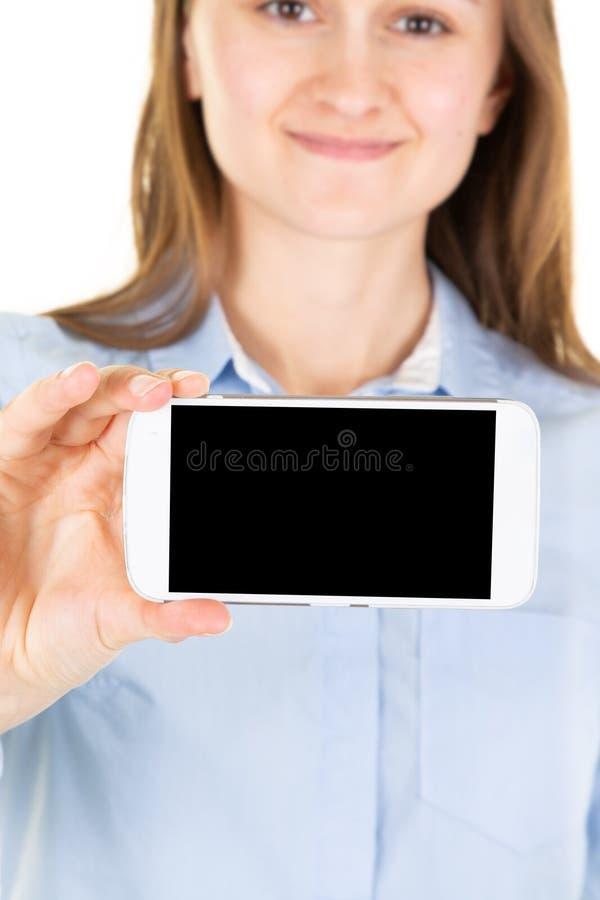 Tiro cosechado del teléfono celular que se sostiene femenino joven con la pantalla negra del copyspace que presenta en la pared e foto de archivo