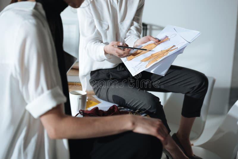 tiro croped dos desenhadores de moda que sentam-se na tabela fotos de stock