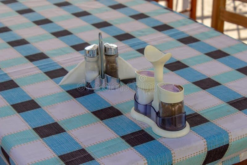 Tiro da adega da pimenta e do sal do close-up na tabela esquadrada do projeto fotos de stock