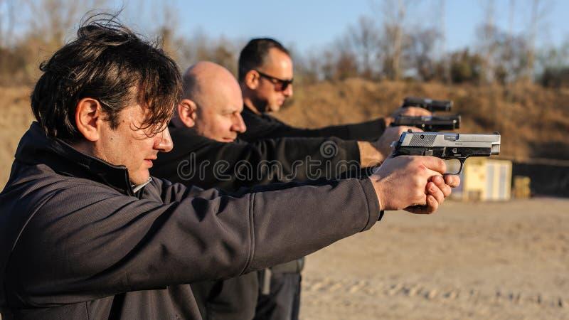Tiro da arma da prática do grupo de pessoas no alvo na escala de tiro exterior imagem de stock