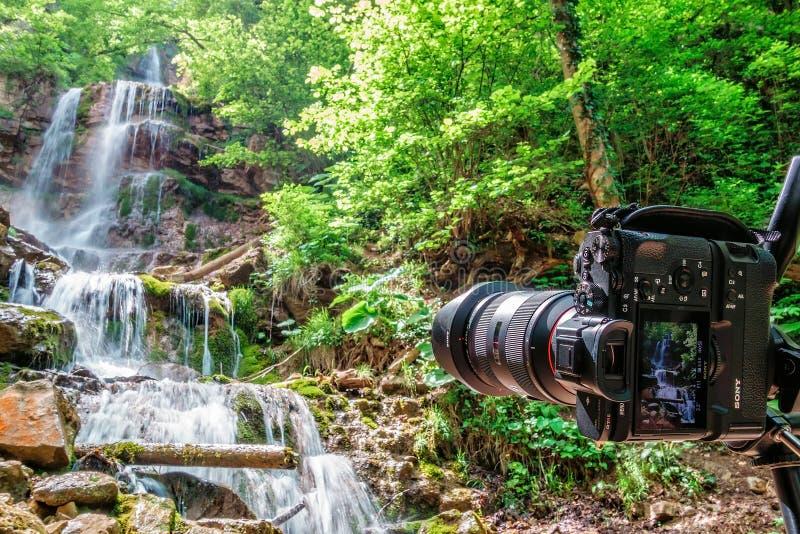 Tiro da cascata da cachoeira com Sony A7RII colocado no tripé em montanhas de Cáucaso pela vila de Mezmay fotografia de stock royalty free