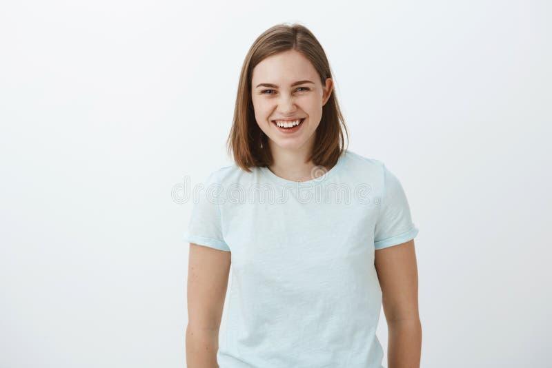 Tiro da cintura-acima da menina moreno ordinária bonita mantida distraído e divertida alegre no t-shirt na moda que ri felizmente fotografia de stock