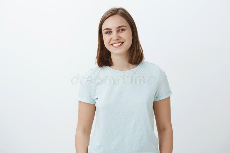 Tiro da cintura-acima da morena fêmea feliz e bonito ambiciosa no t-shirt na moda que sorri alegremente sendo deleitado e satisfe fotografia de stock