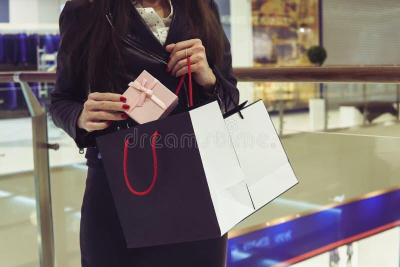 Tiro da colheita da mulher que toma para fora do saco e que mostra a compra nova no fundo do centro de compra Senhora que está pe imagem de stock royalty free