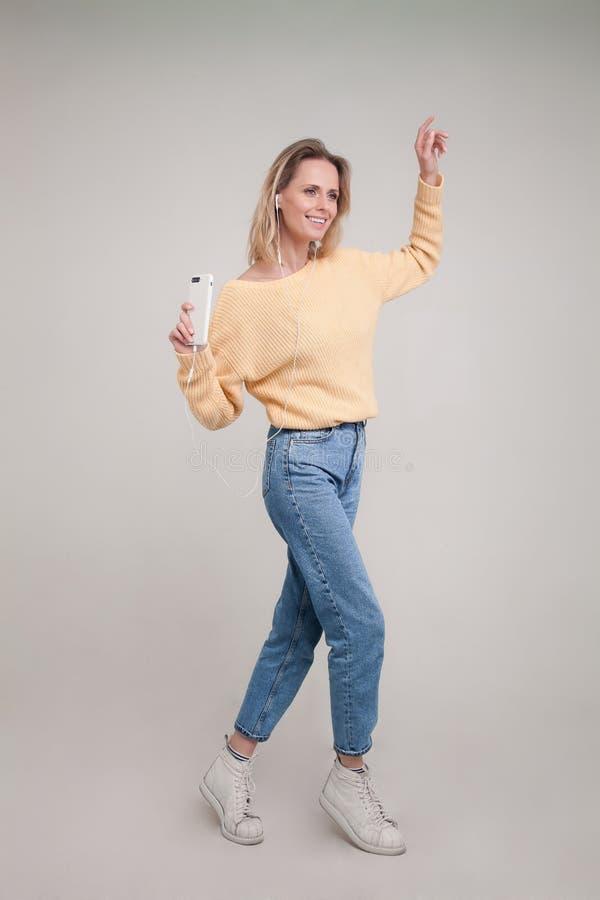 Tiro da dan?a loura nova da mulher ao guardar seu smartphone na m?o tased e ao escutar a m?sica nos fones de ouvido e no sorriso imagens de stock