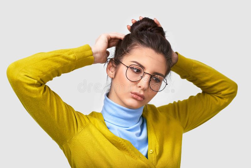 Tiro da jovem mulher bonito com pele limpa saudável, vestindo a camiseta amarela e azul, fazendo um penteado do nó com expressão  foto de stock royalty free
