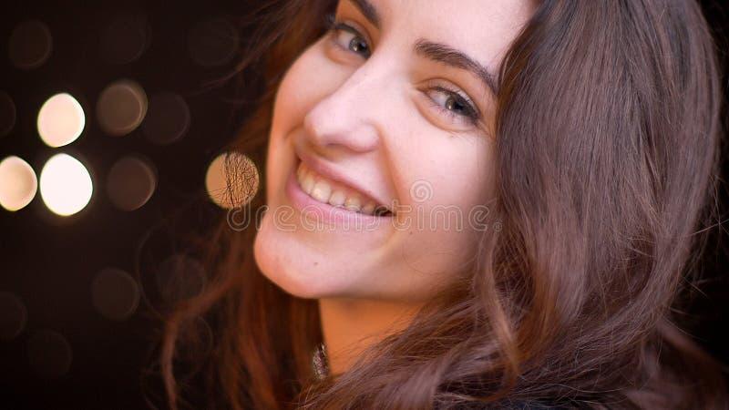 Tiro da opinião lateral do close up da fêmea caucasiano sedutor nova que sorri com encanto ao olhar em linha reta na câmera com imagens de stock