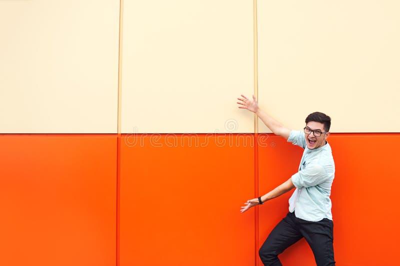 Tiro da posição do homem do smiley contra a parede alaranjada enorme que aponta nela com ambas as mãos que mostram algo foto de stock