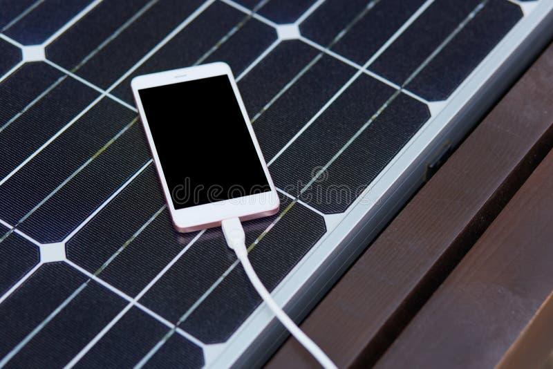 Tiro da vista superior do painel de energias solares instalado no banco de madeira, produzindo a energia, smartphone que é na sup imagem de stock