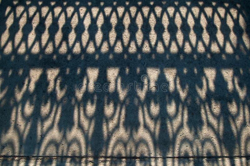 Tiro de ângulo alto da sombra da cerca no crepúsculo, forma fantástica da sombra no assoalho concreto foto de stock royalty free