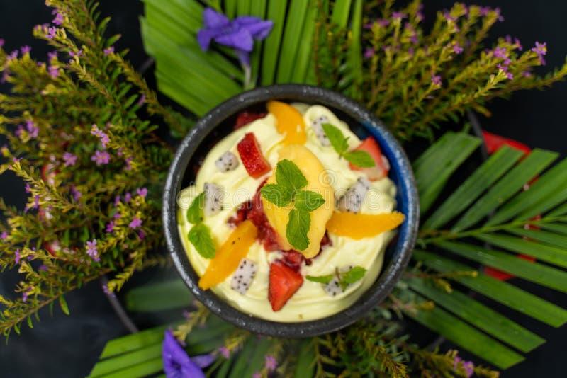 Tiro de ângulo alto do creme com frutos em uma bacia pequena em uma planta fotografia de stock royalty free