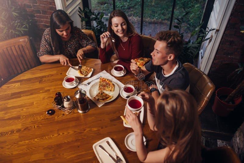 Tiro de alto ángulo del grupo de mejores amigos que cenan en la mesa redonda junto que habla y que sonríe en café acogedor fotografía de archivo libre de regalías