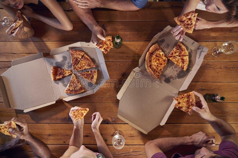 Tiro de arriba de amigos en una tabla que comparte las pizzas para llevar fotos de archivo libres de regalías