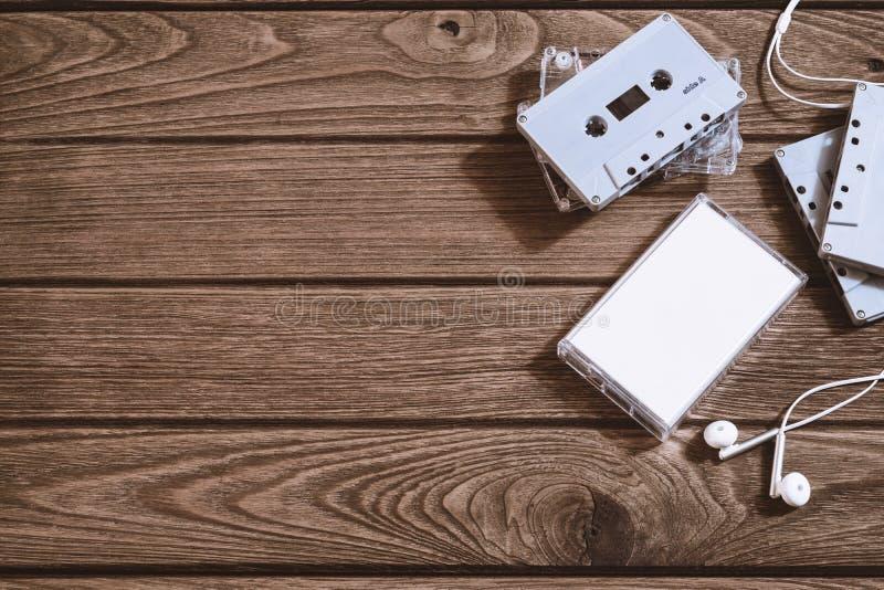 Tiro de arriba de la cinta de casete audio vieja retra con el auricular en el fondo de madera retro del vintage, visión superior  fotos de archivo