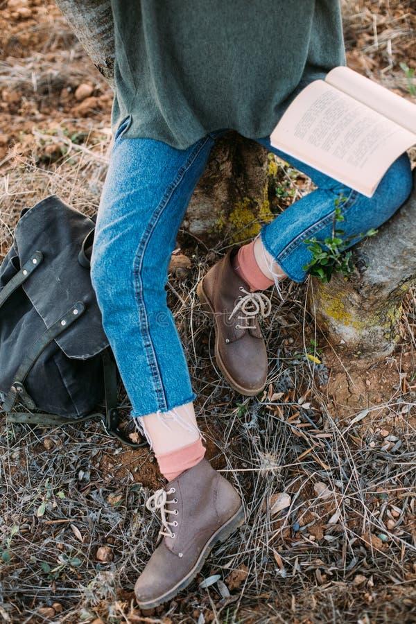 Tiro de arriba de la mujer en botas con el libro fotos de archivo libres de regalías