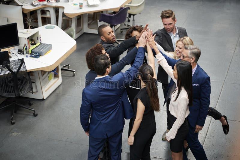Tiro de arriba de la tostada de Team Celebrating Success With Champagne del negocio en oficina moderna imagenes de archivo
