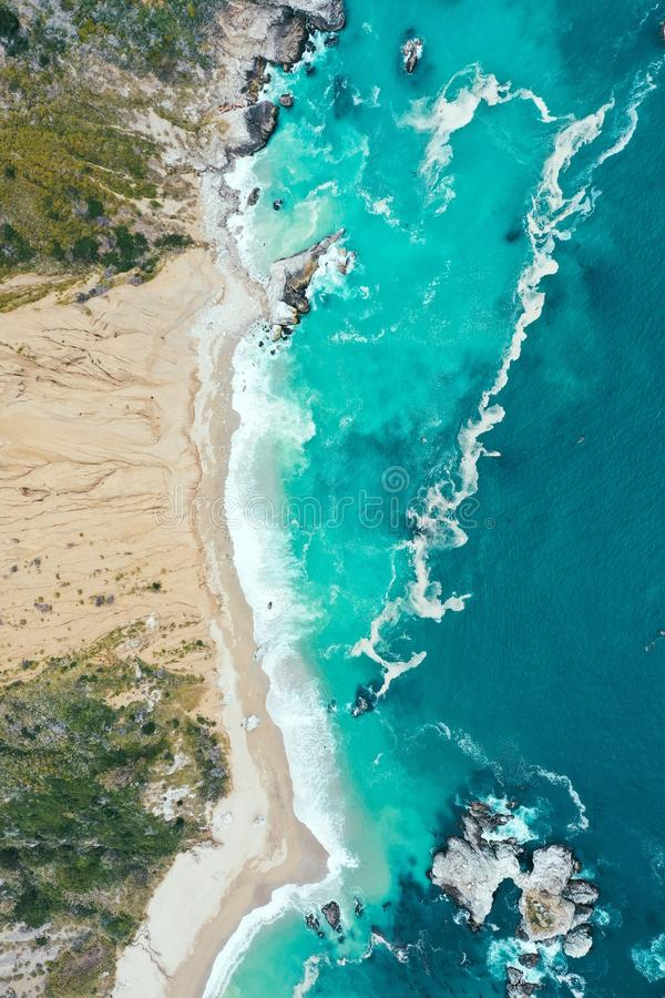 Tiro de arriba vertical de la línea de la playa hermosa del mar con el agua potable azul y la playa arenosa imágenes de archivo libres de regalías