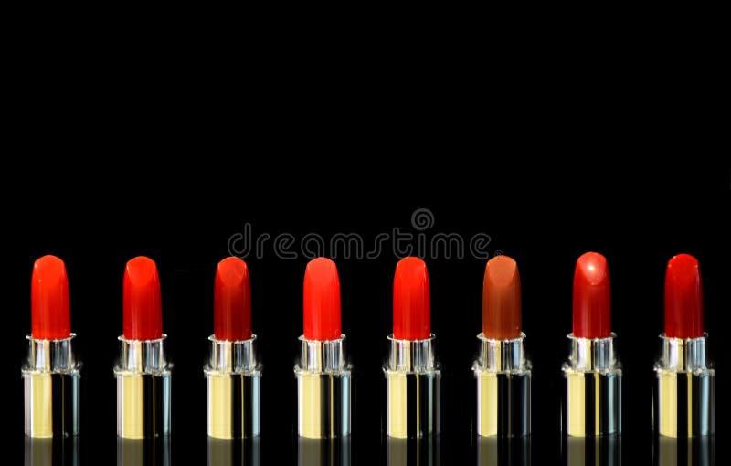Tiro de batons vermelhos da cor diferente No fundo preto Conceito dos cosm?ticos Elevação moderna luxuosa bonita imagem de stock