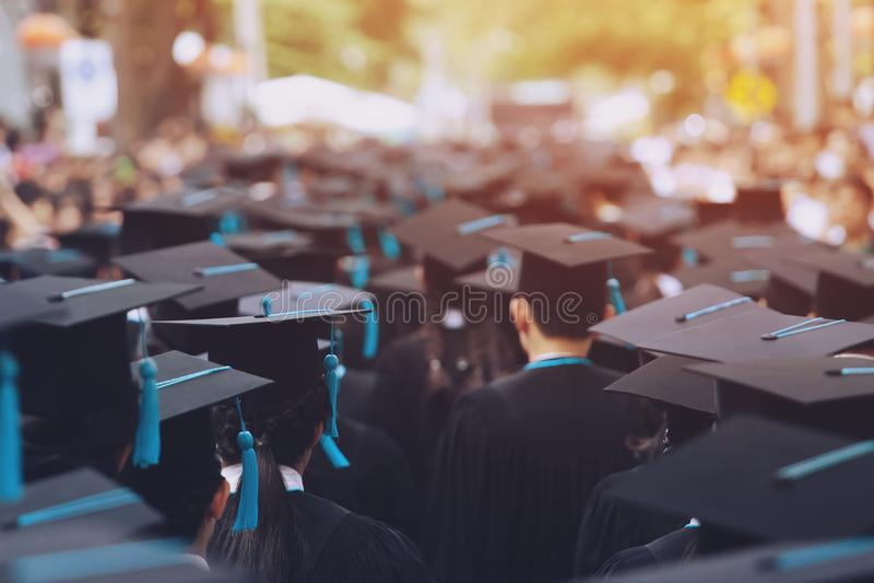 Tiro de chapéus da graduação durante graduados da universidade, jovens do sucesso do começo do estudante das felicitações da educ fotografia de stock royalty free