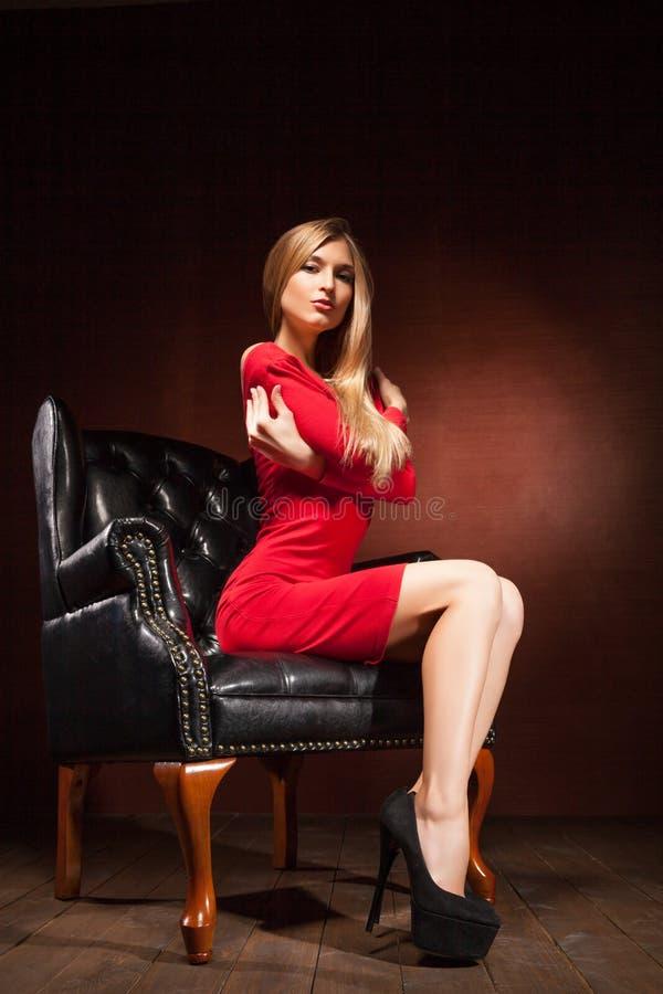 Tiro de la mujer hermosa que lleva la sentada roja del vestido imagen de archivo