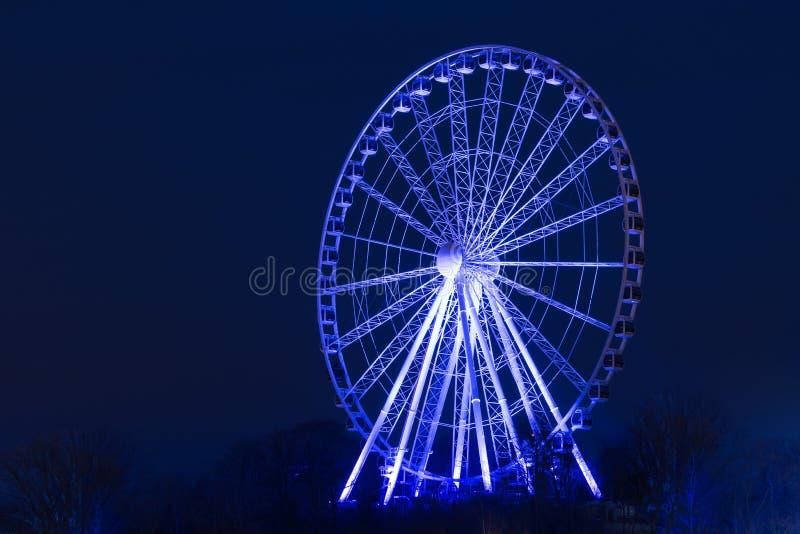 Tiro de la noche de una noria iluminada en azul foto de archivo libre de regalías