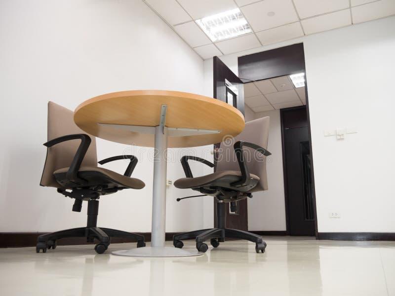 Tiro de la sala de reunión vacía con la mesa redonda y cómodo anchos fotos de archivo libres de regalías