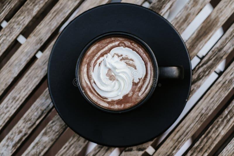 Tiro de la visi?n superior del caf? fresco de la moca caliente en una taza negra con nata montada imagenes de archivo
