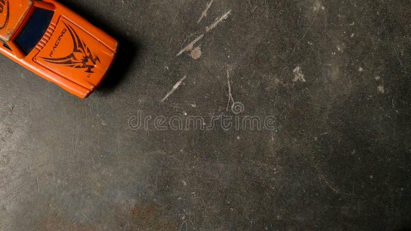 Tiro de la visión superior del capo del coche anaranjado del juguete en fondo limpio imagen de archivo