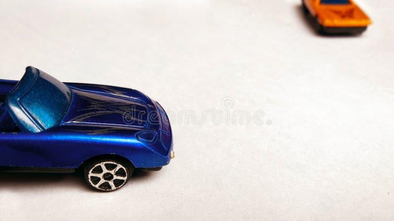 Tiro de la vista lateral del capo del coche azul del juguete en fondo limpio con el coche anaranjado imagenes de archivo