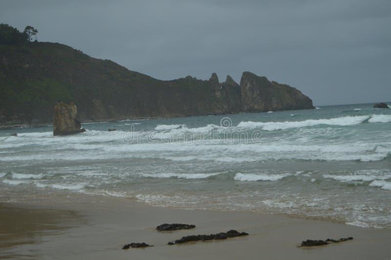 Tiro de las ondas que vienen a la playa y lejos a un EL hermoso Aguilar de Cliff On The Beach Of en un día lluvioso r fotos de archivo