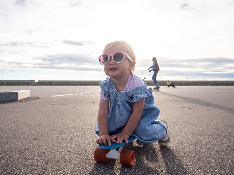 Tiro de Lifstyle: Uma menina feliz em óculos de sol cor-de-rosa e em um vestido azul está sentando-se em uma placa do patim imagem de stock royalty free