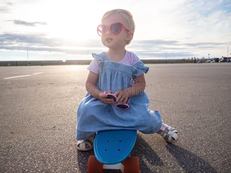 Tiro de Lifstyle: Uma menina feliz em óculos de sol cor-de-rosa e em um vestido azul está sentando-se em uma placa do patim fotos de stock royalty free