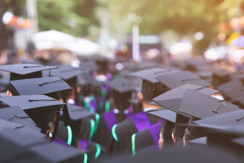 tiro de los sombreros de la graduación durante los graduados de la universidad, jóvenes del estudiante de la enhorabuena de la ed foto de archivo libre de regalías