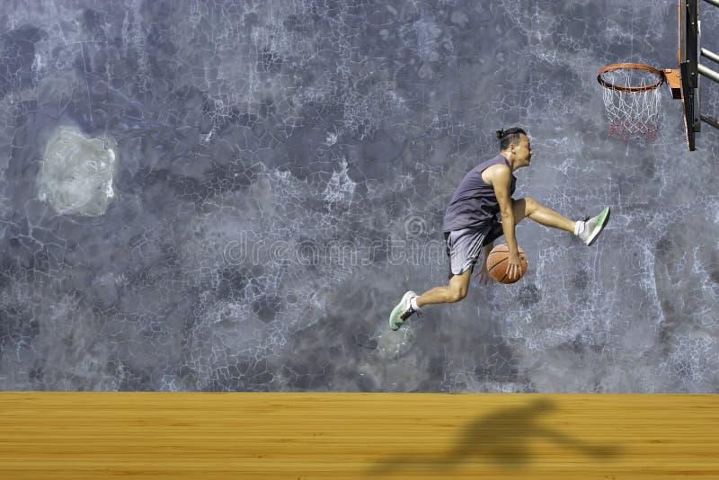 Tiro de salto del hombre disponible del baloncesto un aro de baloncesto en el desv?n de madera de la pared del yeso del fondo del foto de archivo libre de regalías