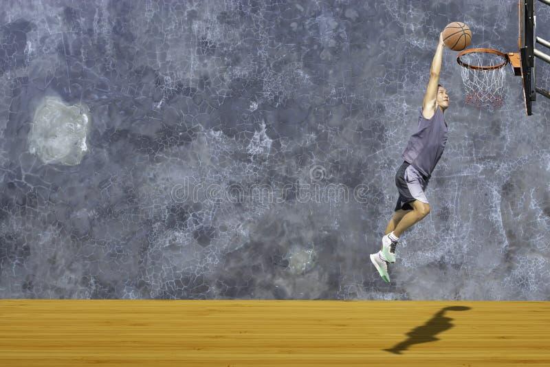 Tiro de salto del hombre disponible del baloncesto un aro de baloncesto en el desv?n de madera de la pared del yeso del fondo del fotografía de archivo