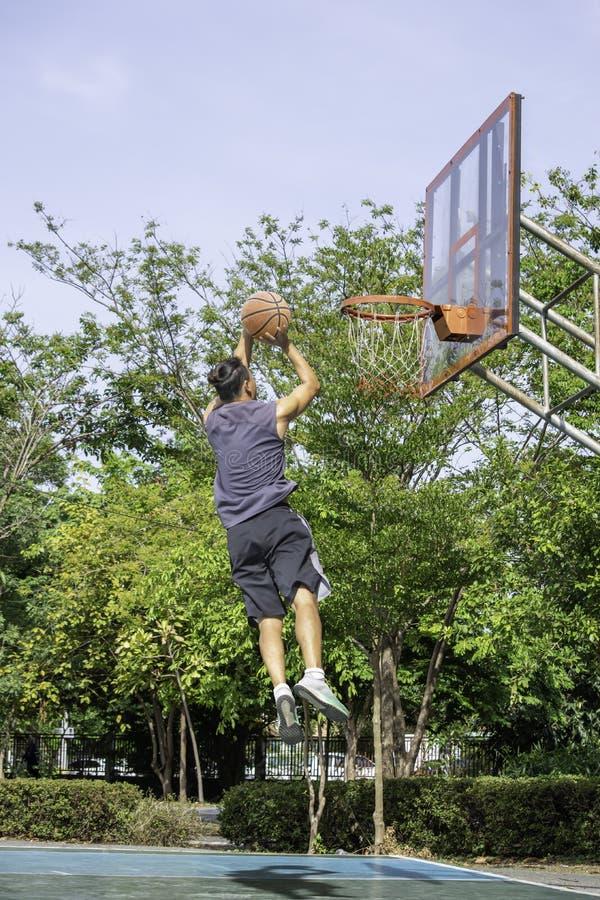 Tiro de salto del hombre disponible del baloncesto un ?rbol del fondo del aro de baloncesto en parque fotografía de archivo libre de regalías