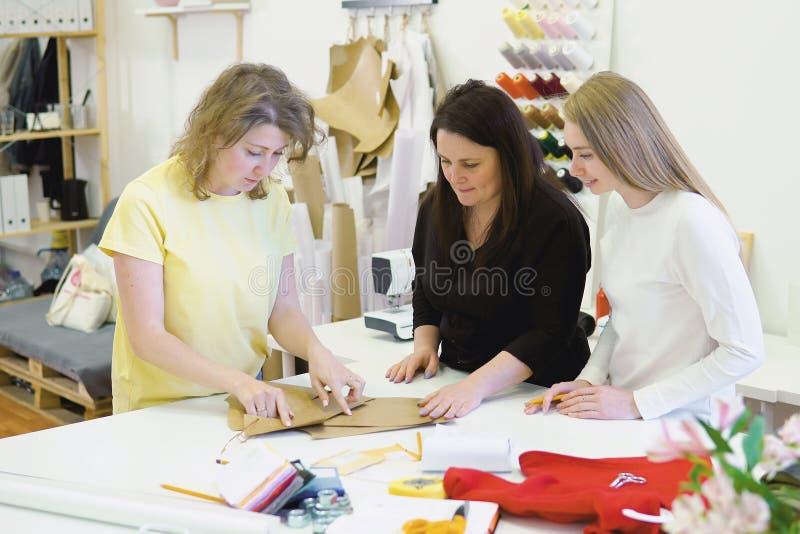 Tiro de três desenhadores de moda que trabalham e que decidem detalhes de coleção nova da roupa na oficina costurando imagens de stock royalty free