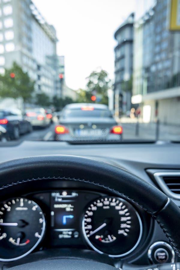 Tiro del concepto del atasco en la ciudad con el primer del volante y de la carlinga borrosa y las calles con el coche durante foto de archivo