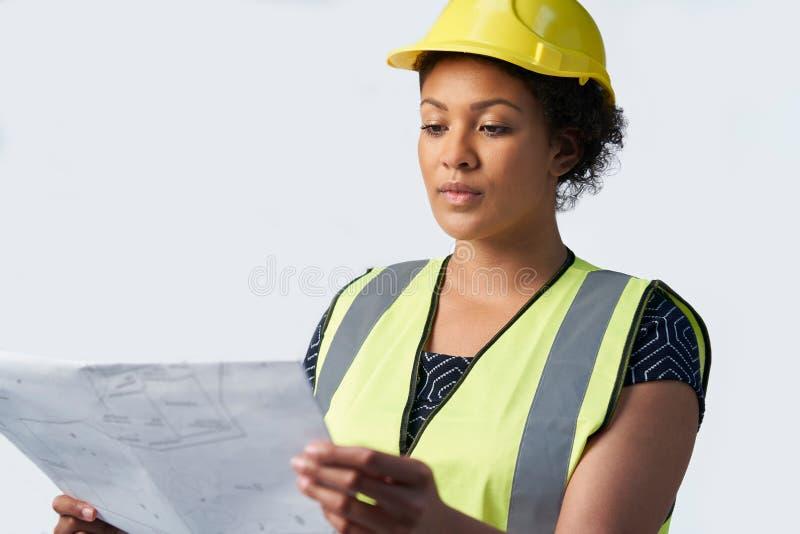 Tiro del estudio del arquitecto de sexo femenino Wearing Hard Hat que estudia planes contra el fondo blanco imagen de archivo libre de regalías