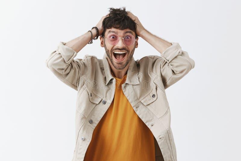 Tiro del estudio de impresionado varón oscuro-cabelludo atractivo emocionado y emocionado en gafas de sol elegantes con la barba  fotos de archivo libres de regalías