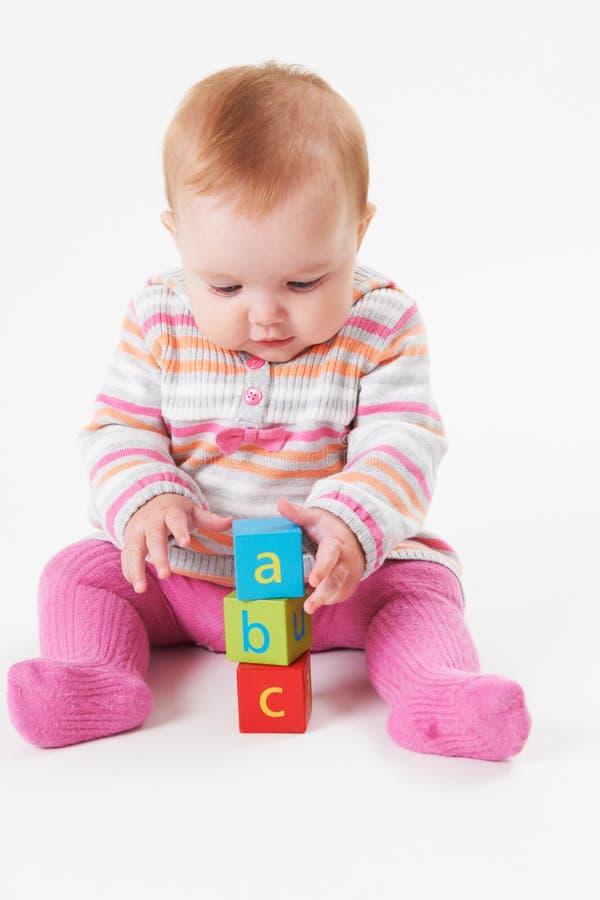 Tiro del estudio de la chica joven que juega con los bloques del alfabeto foto de archivo libre de regalías