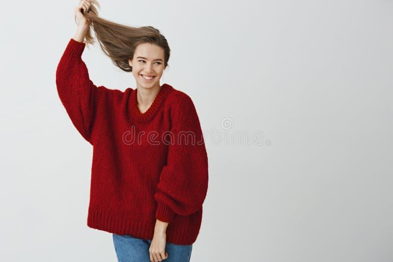 Tiro del estudio de la hembra europea atractiva despreocupada con sonrisa sensual, aumentando el pelo sano hermoso para arriba co foto de archivo