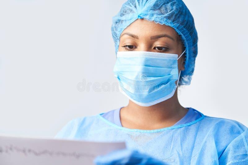 Tiro del estudio de la máscara femenina de Wearing Gown And del cirujano que sostiene la impresión médica hacia fuera fotografía de archivo libre de regalías