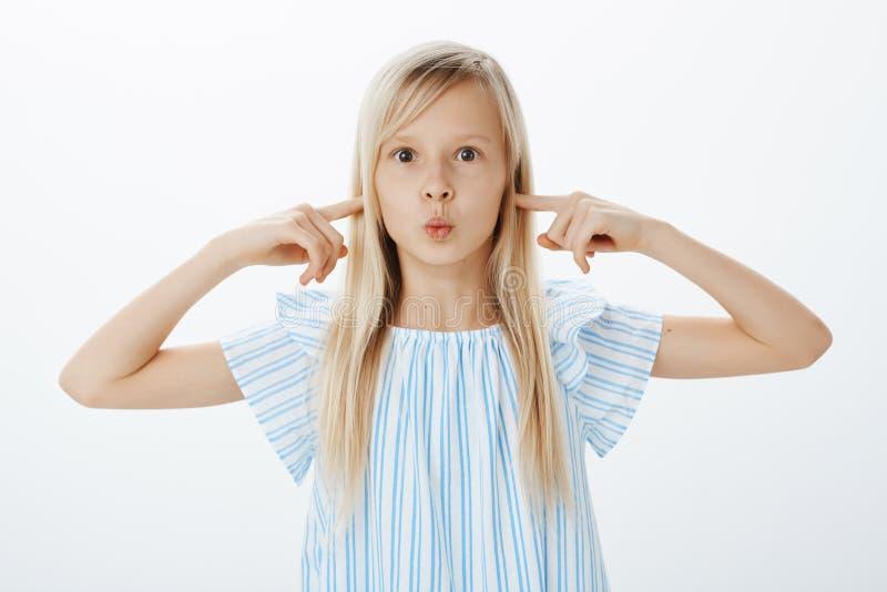 Tiro del estudio de la muchacha linda emocionada abrumada con el pelo rubio, poniendo mala cara con los labios doblados y cubrien fotografía de archivo