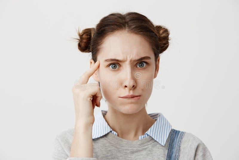 Tiro del estudio de la mujer caucásica pensativa en finger que se sostiene casual en su templo que presenta con mirada significat foto de archivo