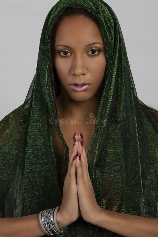 Tiro del estudio de la mujer joven del mulatta con una bufanda verde en la cabeza praing contra el fondo blanco imagenes de archivo